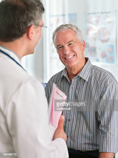 Cheerful male patient with doctor at hospital