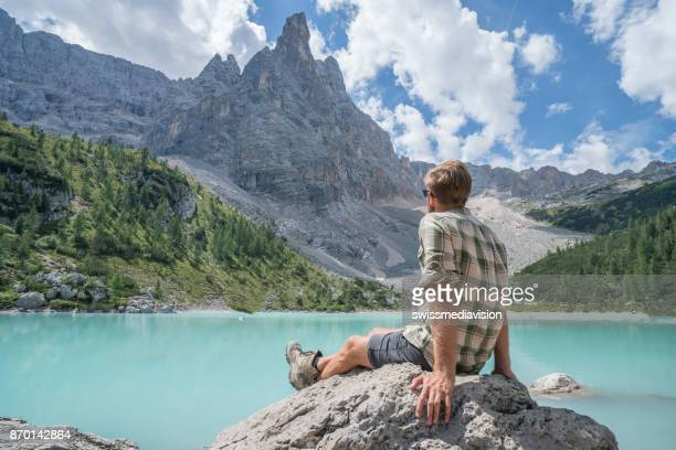 Cheerful male relaxing and contemplating lake Alpine lake in Italy