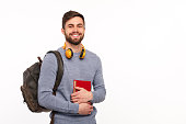 Young handsome man with backpack and headphones holding book and smiling at camera.