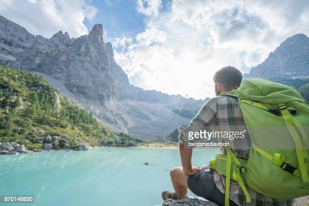 Cheerful man contemplating lake Alpine lake in Italy