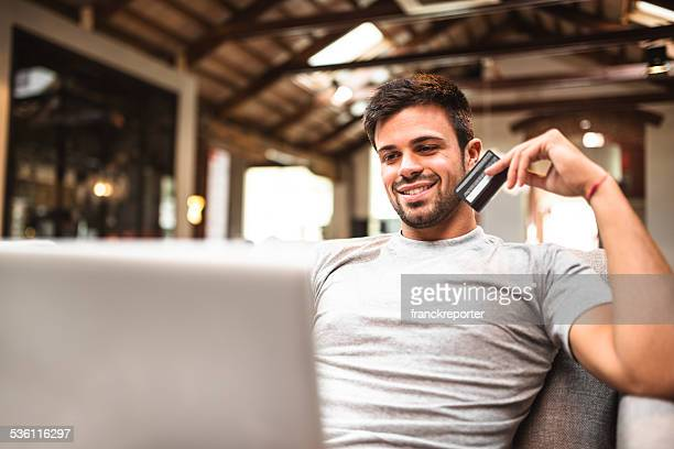 Cheerful man doing the shopping online on sofa