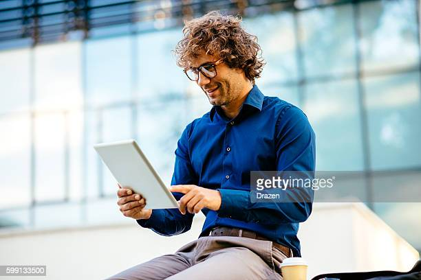 Cheerful man drinking coffee and using digital tablet