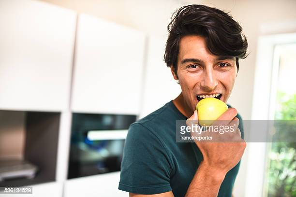cheerful man eating an apple on kitchen