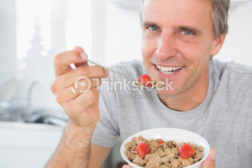Cheerful man eating cereal for breakfast : Foto de stock