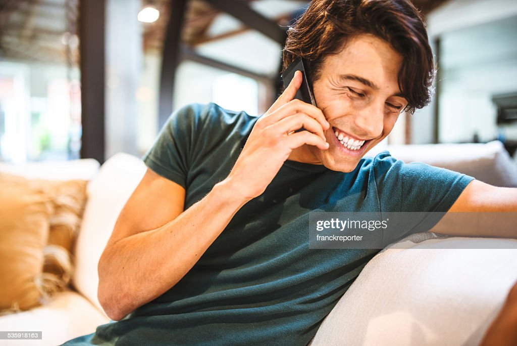 Cheerful man have a phone call on the sofa : Stock Photo