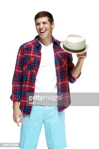 Cheerful man holding fedora & looking away : Bildbanksbilder