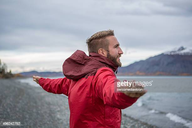 Cheerful man in nature arms outstretched for positive emotion