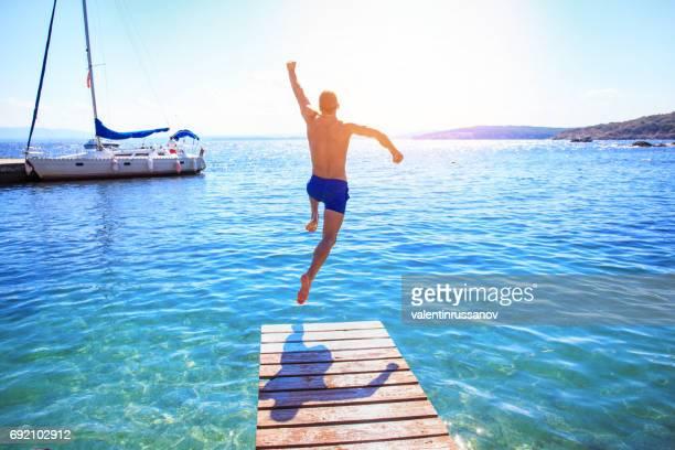 Fröhlicher Mensch Sprung ins Wasser