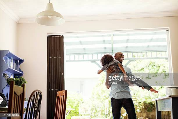 Cheerful man lifting boy at home