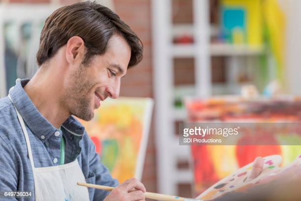 Cheerful man mixes paint on artist's palette