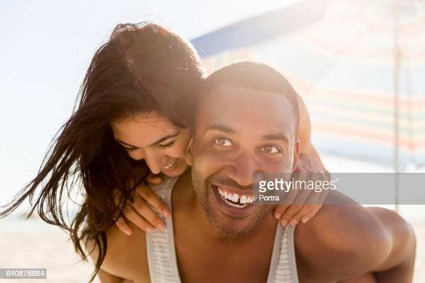 Cheerful man piggybacking girlfriend at beach