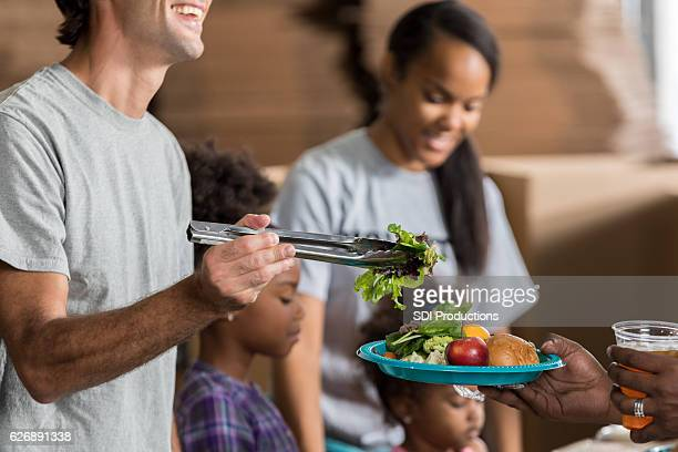 Cheerful man serves meal in soup kitchen