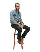 Cheerful man sitting on stool