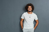 Portrait of happy young man with curly hair standing against grey background. African man with hands in pocket leaning against grey wall. Multi ethnic young man in casual looking at camera with copy s