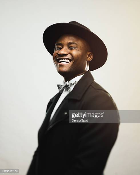 Cheerful man wearing black suit and hat