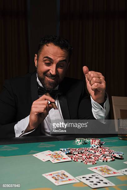 Cheerful man winning at the poker table