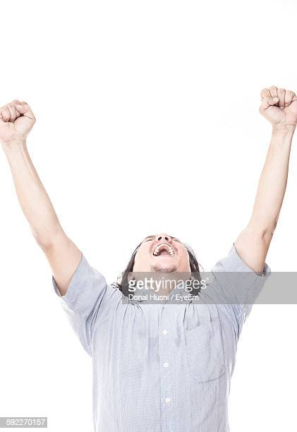 Cheerful Man With Arms Raised Against White Background