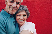 Portrait of cheerful middle aged couple embracing each other against red background. Mature man and woman together against red wall.