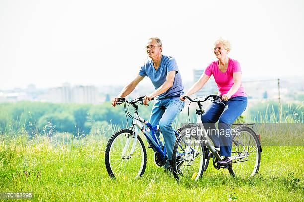 Cheerful mature couple riding bicycles in park.
