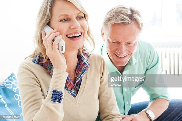 Cheerful mature couple speaking on a phone