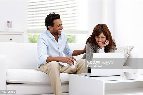 Joyeux couple d'âge mûr à l'aide d'ordinateur portable à la maison