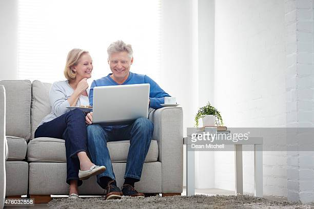 Cheerful mature couple using laptop computer at home