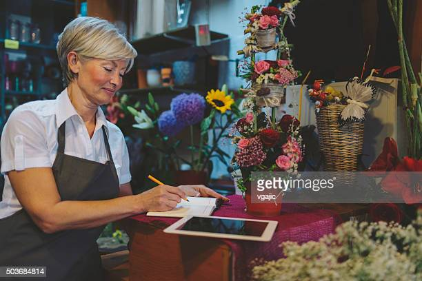 Cheerful mature florist making order