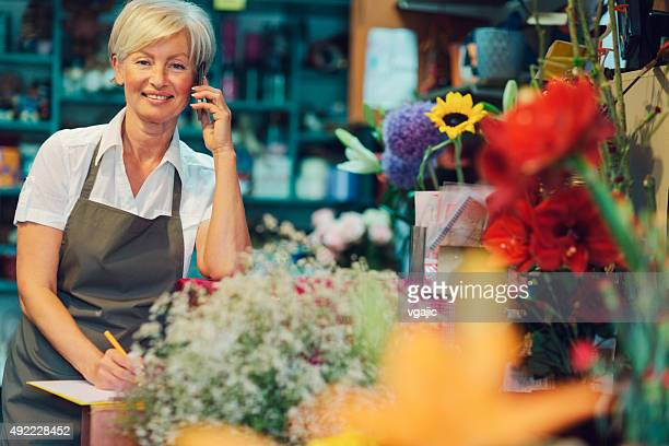 Cheerful mature florist talking on the phone in her shop.