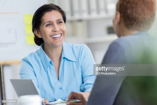 Cheerful mature Hispanic businesswoman meets with client