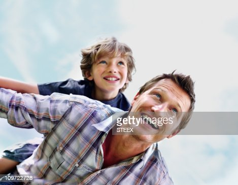 Cheerful mature man with son on back flying against sky : Stock Photo