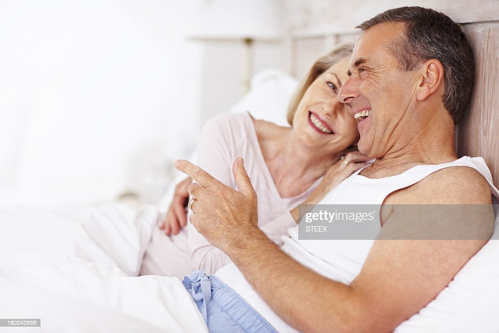 Cheerful mature man with wife lying in bed : Stock Photo