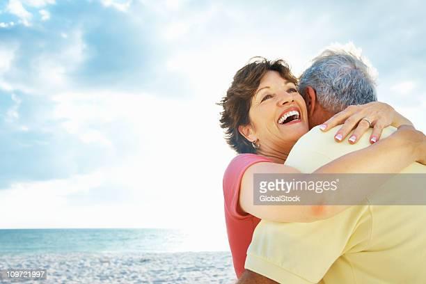 Cheerful mature woman embracing a senior man against sky