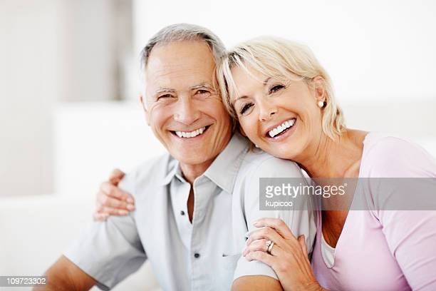 Cheerful mature woman embracing senior man against white