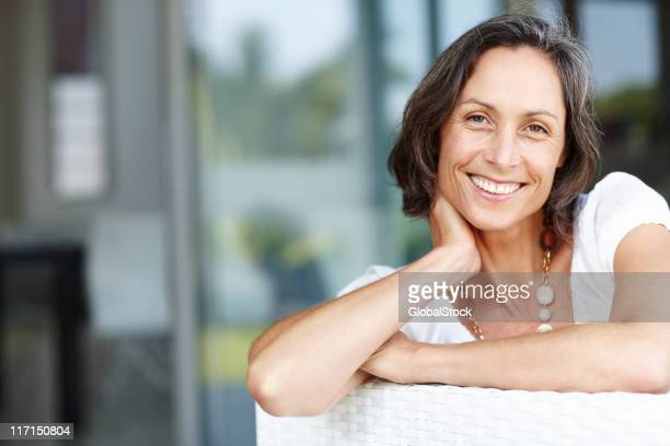 Cheerful mature woman relaxing on a couch