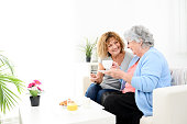 cheerful mature woman serving breakfast and taking care of elderly senior woman at home