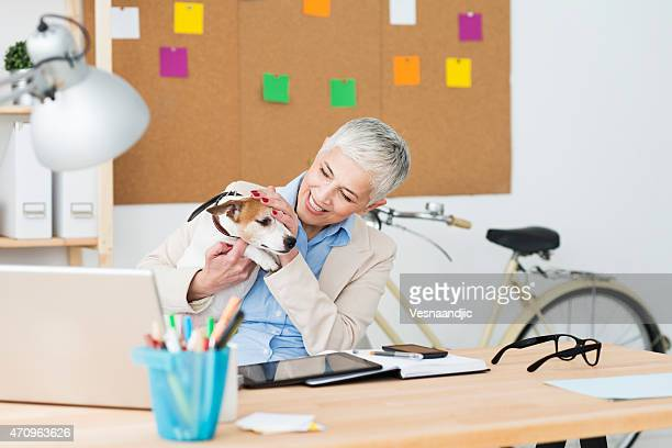 Cheerful mature woman with her pet at office