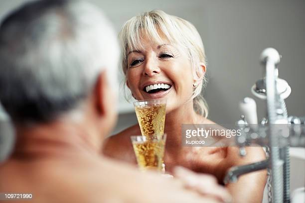 Cheerful mature woman with man toasting champagne glasses