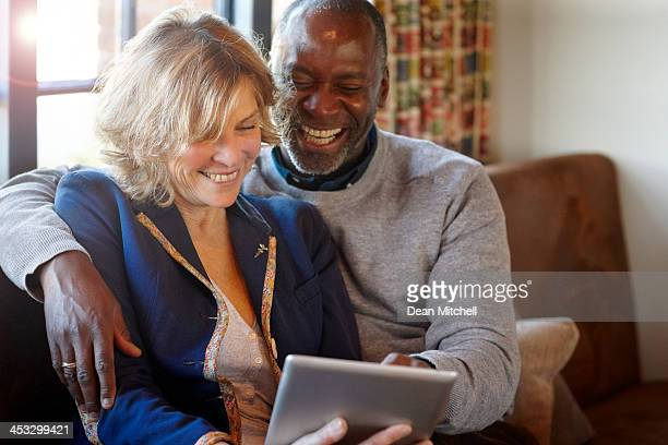 Cheerful middle aged couple in a restaurant using digital tablet