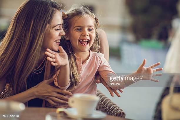 Fröhlich Mutter und Tochter haben Spaß zusammen in einem Café.
