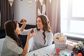 Cheerful mother and daughter prepare for Easter. They hold chocolate eggs and smile. Decoration on table. Model wear white rabbit ears