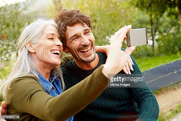 Cheerful mother and son taking selfie in park