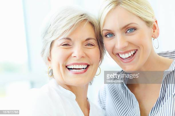 Cheerful mother and young woman with heads together