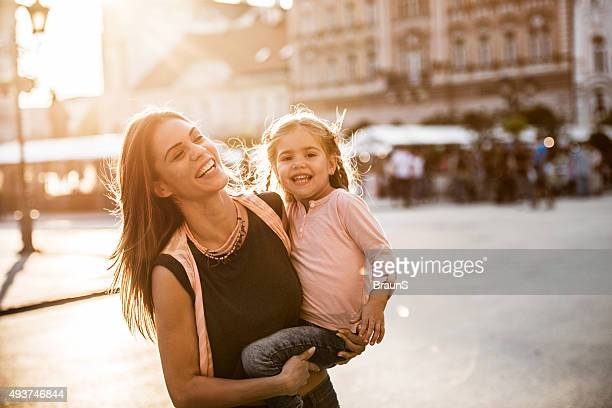 Cheerful mother enjoying with her daughter in the city.