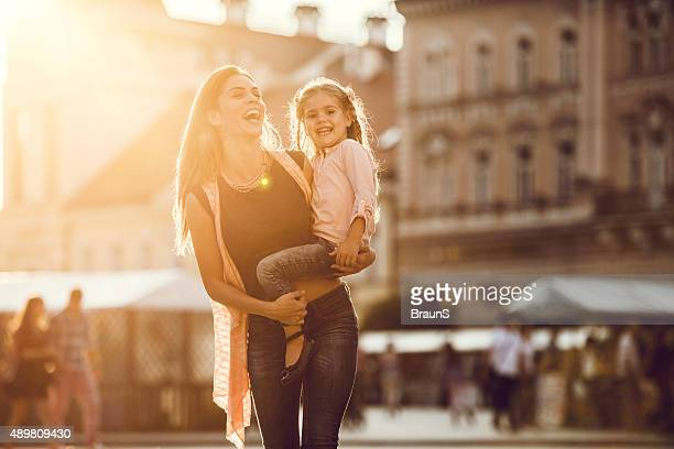 Cheerful mother taking a walk with her daughter outdoors.