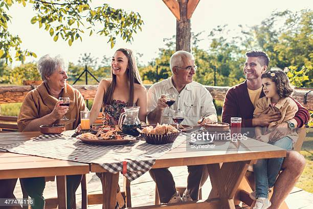 Cheerful multi-generation family having lunch on restaurant terrace.