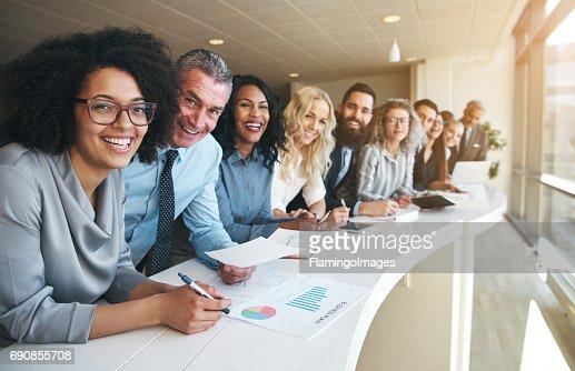 Alegres compañeros multirraciales mirando a cámara en la oficina : Foto de stock