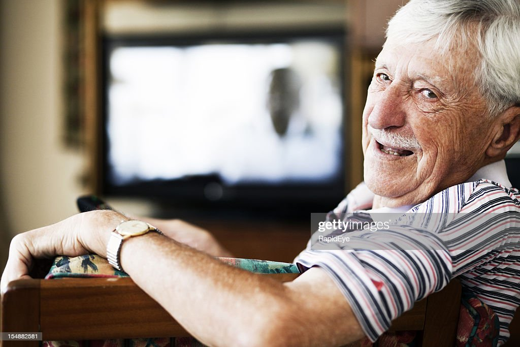 Cheerful old man looks round from watching television