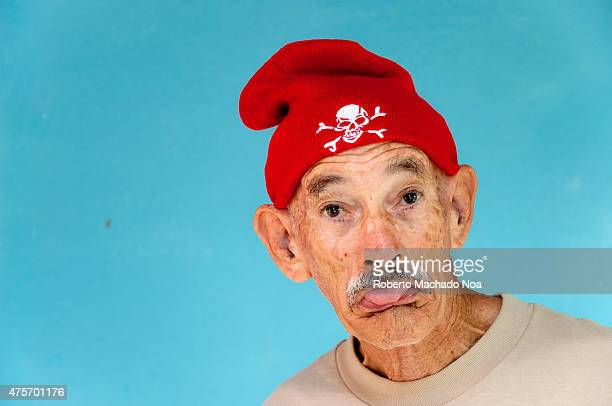 Cheerful old senior man shows tongue with a red cap on his head Cap with a white skull and crossbones Jolly Roger Blue background