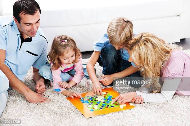 Cheerful parents playing board game with their children.