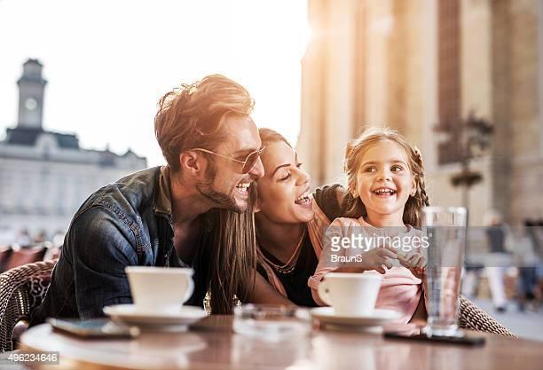 Fröhlich Eltern sprechen Ihre kleine Tochter in einem Café.